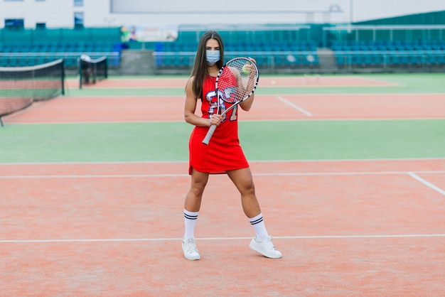 Porträt des tennisspielermädchens, das schläger außerhalb mit schutzmaske hält