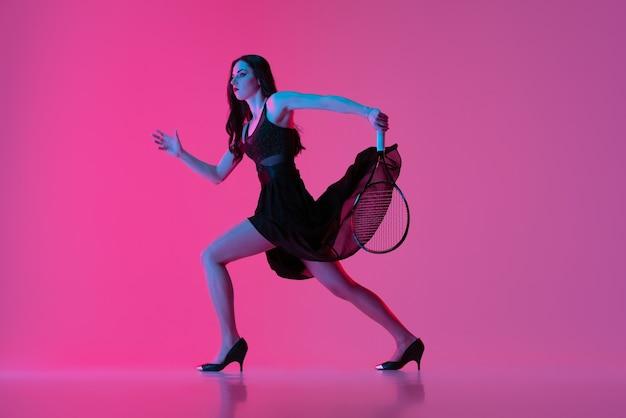 Porträt des tennisspielers der jungen frau im feiertagskleid, das auf dunkelrosa hintergrund läuft.