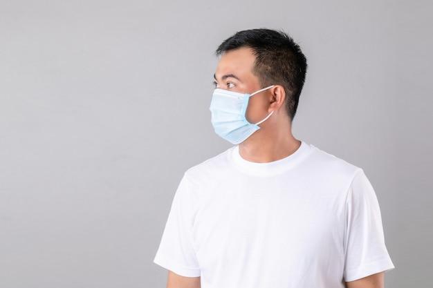 Porträt des thailändischen mannes, der eine schützende gesichtsmaske trägt