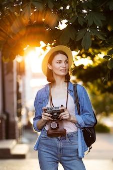 Porträt des touristen mit hut, der kamera hält