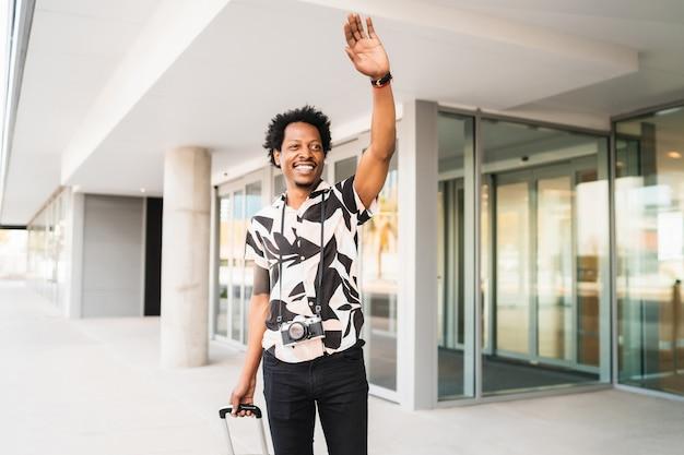 Porträt des touristenmannes, der koffer trägt und seine hand hebt, um ein taxi zu rufen, während man draußen auf der straße geht