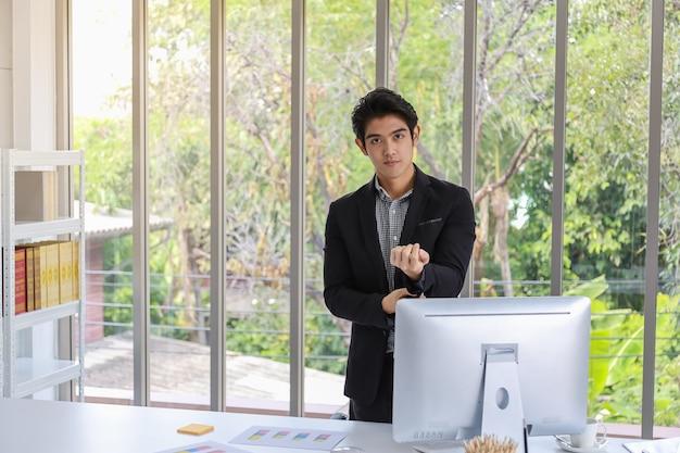 Porträt des tragenden anzugs des intelligenten jungen asiatischen geschäftsmannes im büro mit computer- und papierbalkendiagrammbericht. bild für geschäfts- und arbeitskonzept.
