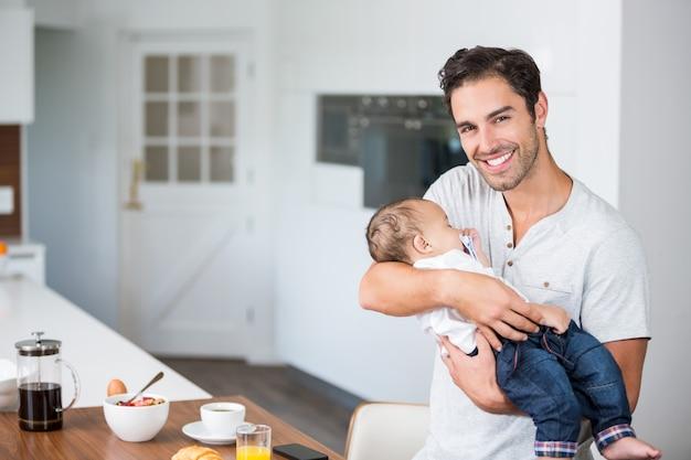 Porträt des tragenden babys des glücklichen vaters