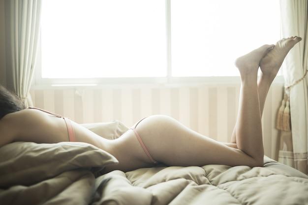 Porträt des tragenden bikinis der sexy jungen frau modell im schlafzimmer
