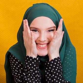 Porträt des tragenden hijab der glücklichen moslemischen frau, das kamera betrachtet
