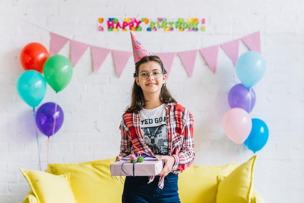 Porträt des tragenden partyhutes des glücklichen mädchens, der geburtstagsgeschenk hält
