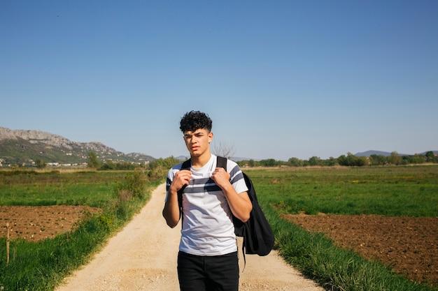 Porträt des tragenden rucksacks des jungen mannes