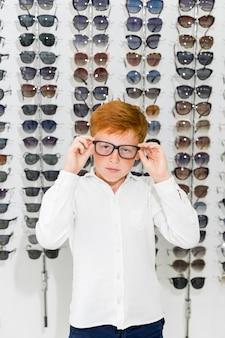 Porträt des tragenden schauspiels des netten jungen, das gegen brillengestell im optikshop steht