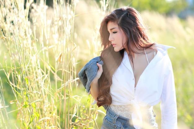 Porträt des tragenden weißen hemdes der schönheit und des blauen baumwollstoffs, die eine glückliche zeit haben und unter rasenfläche in der natur genießen
