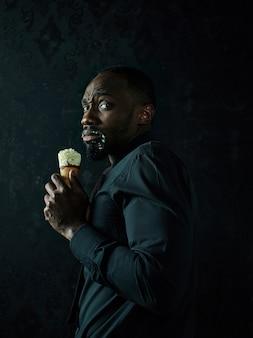 Porträt des traurigen afroamerikanischen mannes, der eiscreme über schwarzem studiohintergrund hält