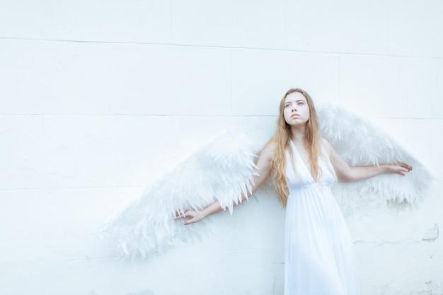 Porträt des traurigen engelsmädchens mit den großen weißen flügeln nahe der weißen wand