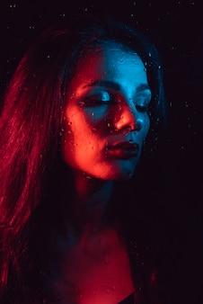 Porträt des traurigen jungen mädchens mit roter blauer beleuchtung hinter glas mit regentropfen