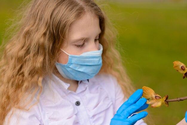 Porträt des traurigen kaukasischen kindes in der gesichtsmaske auf geschlossenem spielplatz im freien. quarantäne für soziale distanz von coronavirus.