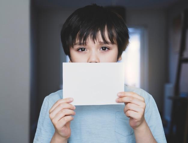 Porträt des traurigen kindes, das leeres weißes papier hält, einsamer kinderjunge, der weißes papier ohne die wörter zeigt
