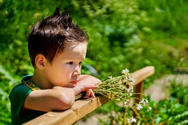 Porträt des traurigen kleinen jungen, der zur tageszeit auf der brücke steht