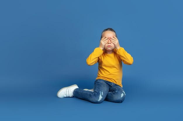 Porträt des traurigen kleinen mädchensitzens lokalisiert auf blauem studiohintergrund. wie es sich anfühlt, autist zu sein. moderne probleme, neue vision von sozialen fragen. konzept von autismus, kindheit, gesundheitswesen, medizin.