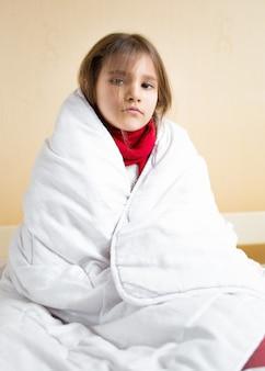 Porträt des traurigen kranken mädchens, das mit weißer decke bedeckt