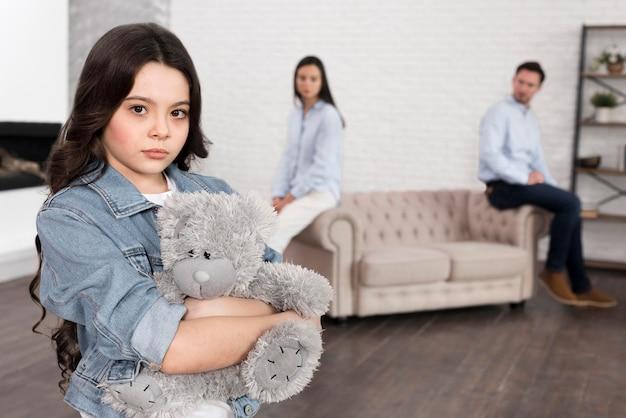 Porträt des traurigen mädchens, das teddybär hält