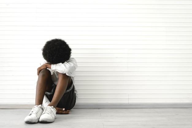 Porträt des traurigen niedlichen kleinen jungen, der auf boden zu hause sitzt