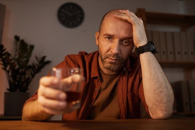 Porträt des traurigen reifen mannes, der am tisch sitzt und kamera mit alkoholgetränk betrachtet