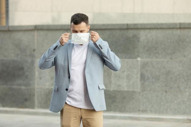 Porträt des trendigen mannes, der eine schutzmaske trägt und in der stadt geht