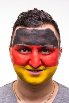 Porträt des treuen fans des hübschen mannanhängers der deutschen nationalmannschaft mit gemaltem flaggengesicht lokalisiert auf weiß. fans emotionen.