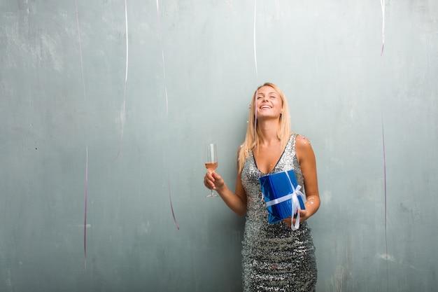 Porträt des trinkenden champagners der eleganten jungen blonden frau und halten eines geschenks, neues jahr mit konfetti feiernd.