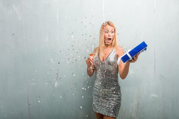 Porträt des trinkenden champagners der eleganten jungen blondine und anhalten eines geschenks