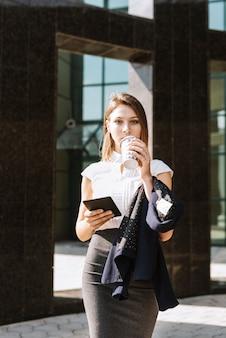 Porträt des trinkenden kaffees der jungen geschäftsfrau, der jacke und smartphone hält
