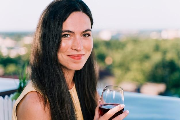 Porträt des trinkenden weins der frau auf der dachspitze
