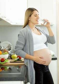 Porträt des trinkwassers der schwangeren frau auf küche