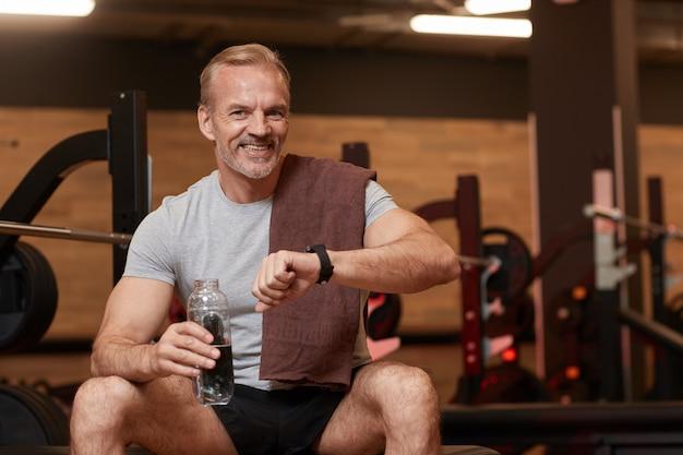 Porträt des trinkwassers des reifen mannes, der seine uhr betrachtet und kamera nach sporttraining im fitnessstudio lächelt