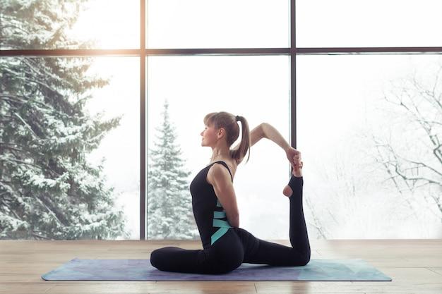 Porträt des übenden yoga der jungen frau innen