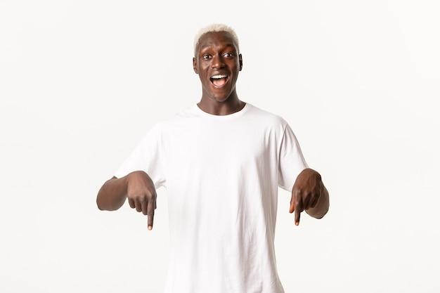 Porträt des überraschten afroamerikanischen blonden kerls, der erstaunliches logo zeigt, amüsiert lächelt und finger nach unten zeigt