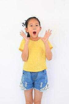 Porträt des überraschten asiatischen mädchens des kleinen kindes lokalisiert auf weißem hintergrund. kind schaut in die kamera und die hände öffnen sich weit