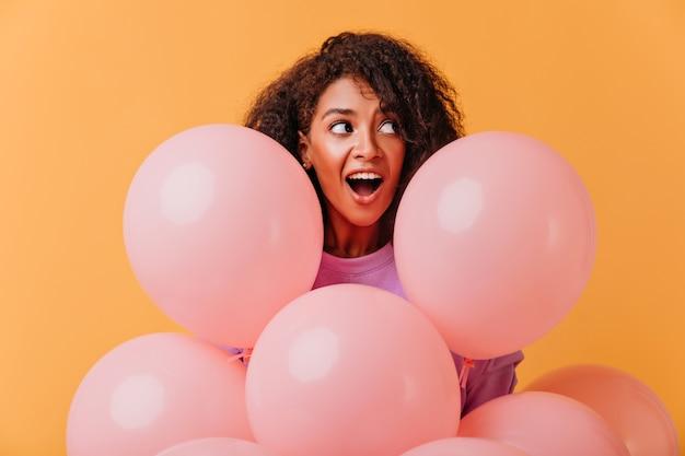 Porträt des überraschten geburtstagsmädchens, das weg schaut, während sie mit luftballons aufwirft. lustige afrikanische dame, die während der partei herumalbert.