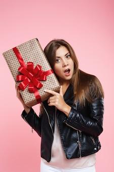 Porträt des überraschten mädchens im trendigen blick, der geschenkbox hält