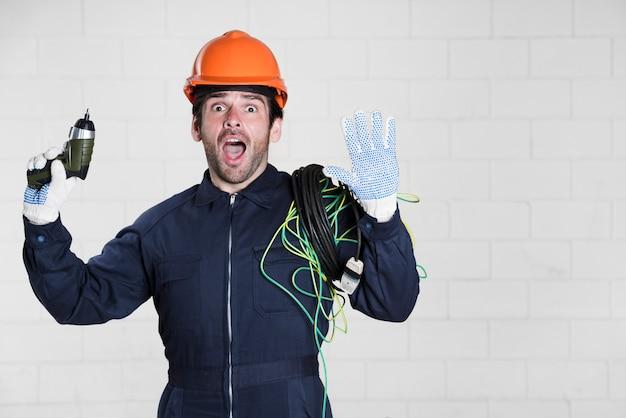 Porträt des überraschten männlichen elektrikers, der kamera mit dem mund offen betrachtet