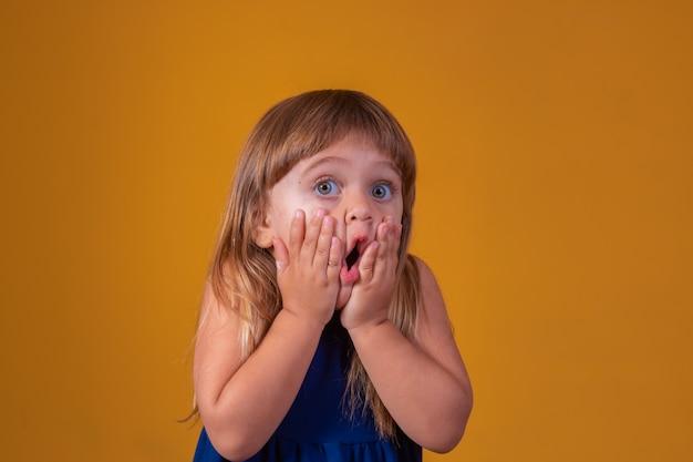 Porträt des überraschten netten kleinen kleinkindmädchenkindes, das lokalisiert über gelbem hintergrund steht. blick in die kamera. hände in der nähe von offenem mund