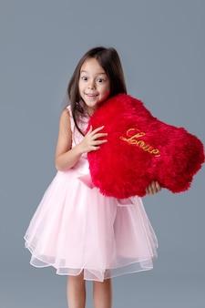 Porträt des überraschten niedlichen kleinen mädchens in einem rosa kleid, das großes rotes herz hält