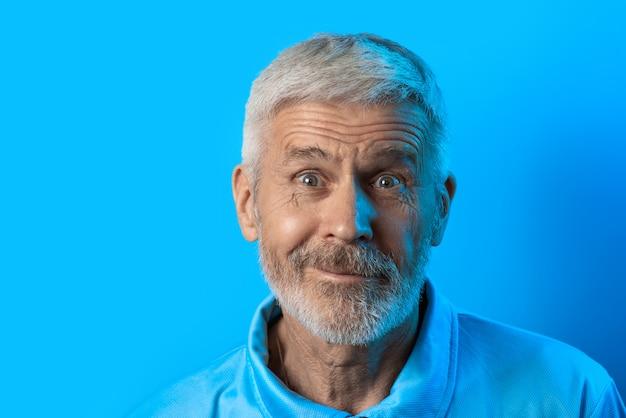 Porträt des überraschten und neugierigen grauhaarigen mannes mit einem bart auf blau