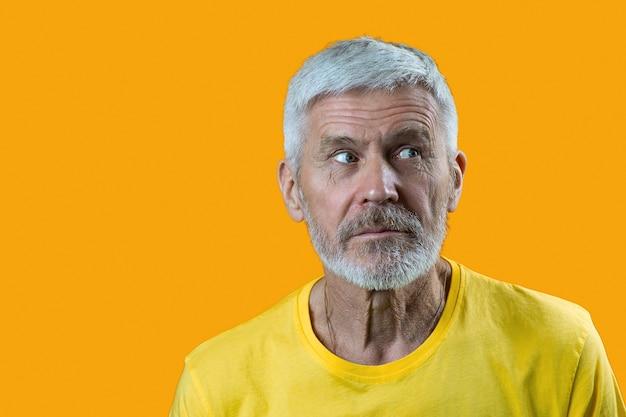 Porträt des überraschten und neugierigen grauhaarigen mannes mit einem bart auf gelb