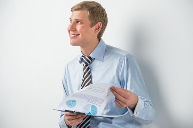 Porträt des überzeugten geschäftsmannes dokument halten und beim lehnen auf der wand in seinem büro denken