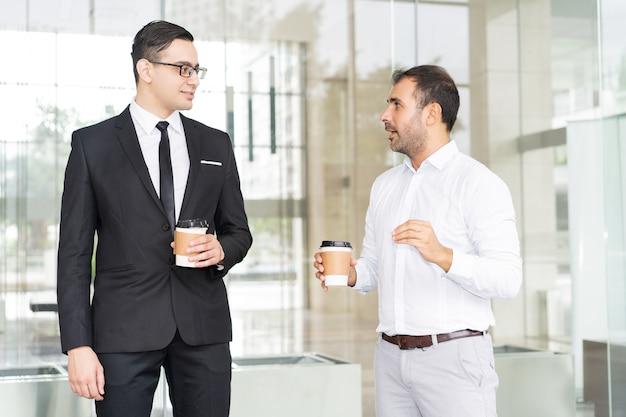 Porträt des überzeugten geschäftsmanntreffens an der kaffeepause
