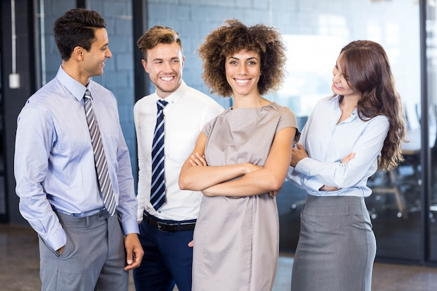 Porträt des überzeugten geschäftsteams, das im büro mit ihren händen gekreuzt steht