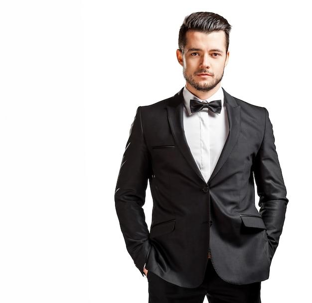 Porträt des überzeugten gutaussehenden mannes im schwarzen anzug mit fliege