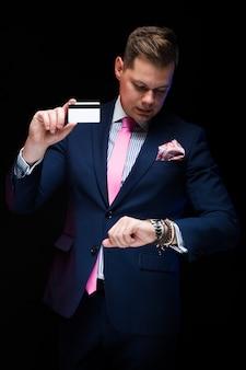 Porträt des überzeugten hübschen eleganten geschäftsmannes, der kreditkarte in seiner hand schaut auf uhren auf schwarzem hintergrund hält