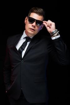 Porträt des überzeugten hübschen eleganten geschäftsmannes in der sonnenbrille auf schwarzem