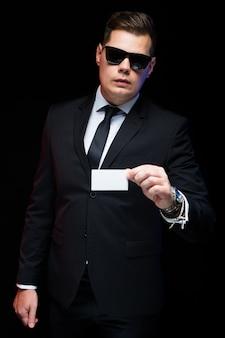 Porträt des überzeugten hübschen eleganten geschäftsmannes in der sonnenbrille, die leere visitenkarte in seiner hand hält