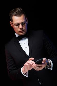 Porträt des überzeugten hübschen eleganten stilvollen geschäftsmannes mit bowtie in den gläsern, die telefon in seinen händen halten